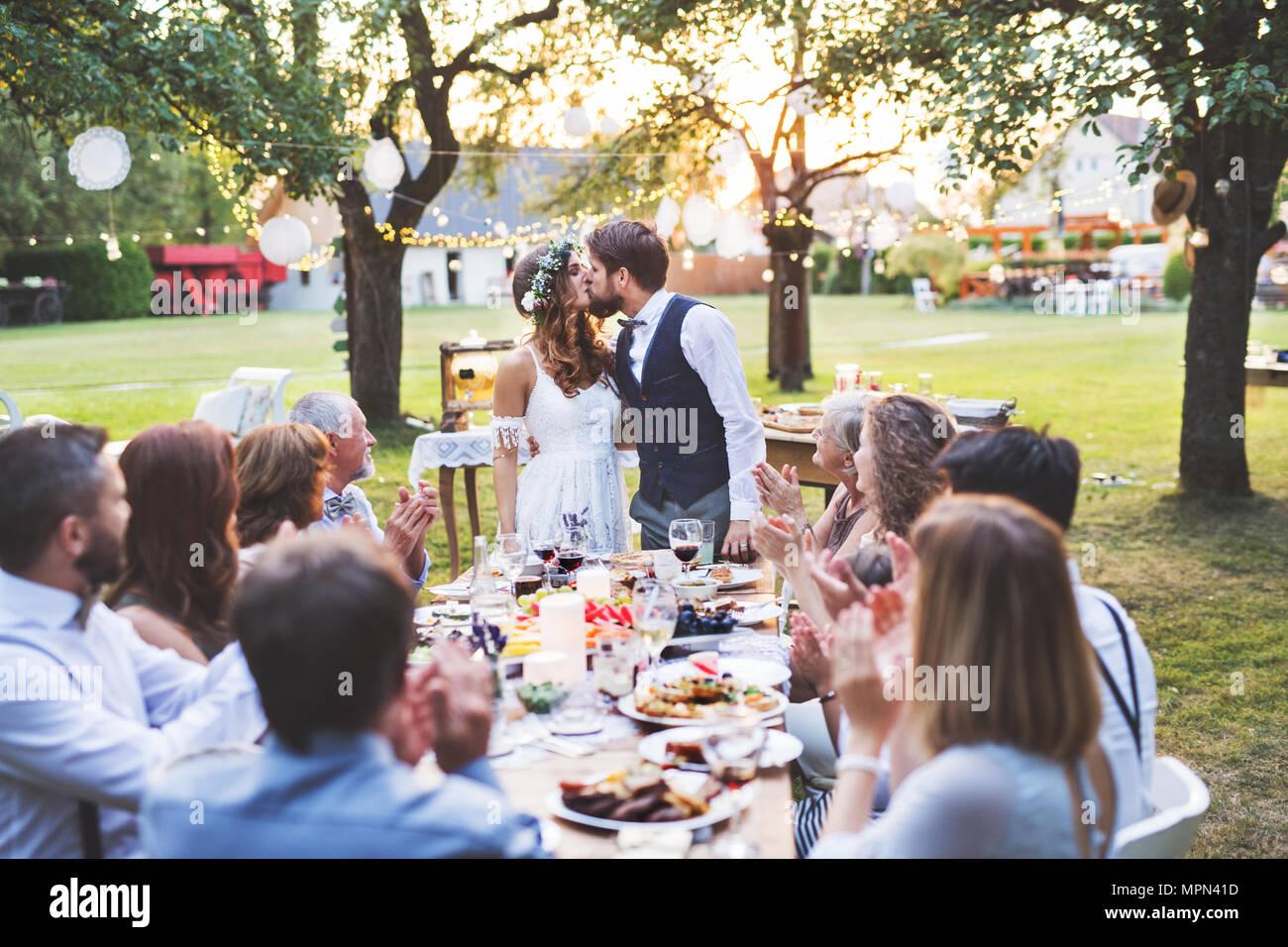 Mariée et le marié avec les clients de réception de mariage à l'extérieur dans la cour. Photo Stock