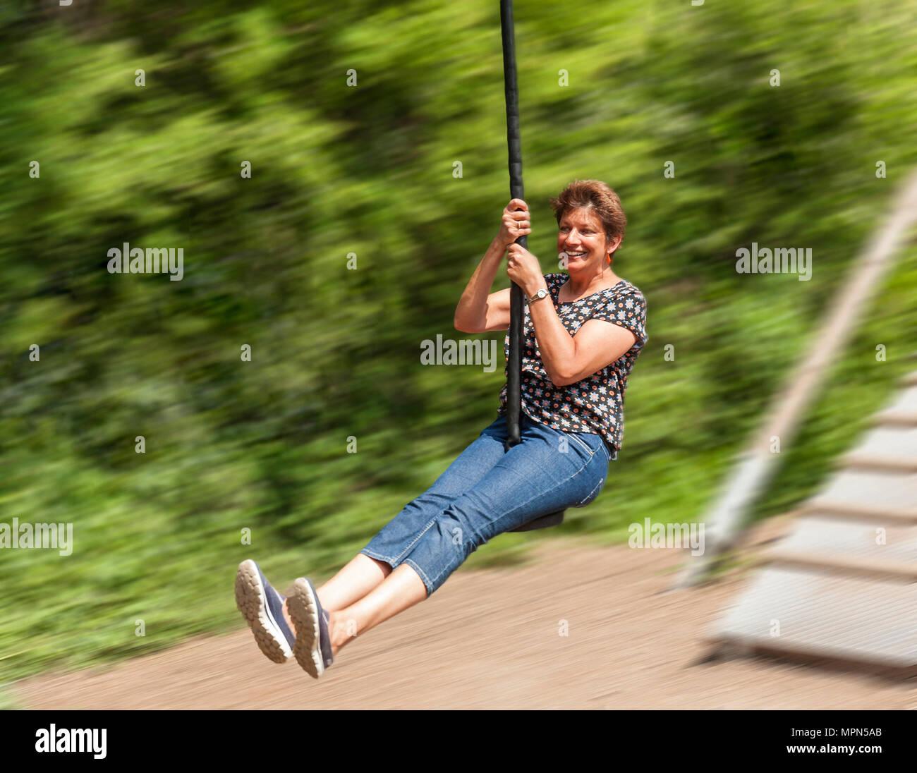 Femme d'âge moyen sur un zip sur le fil. Photo Stock