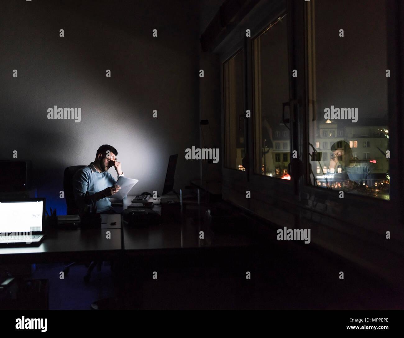 Épuisé businessman sitting at desk dans son bureau par nuit Photo Stock