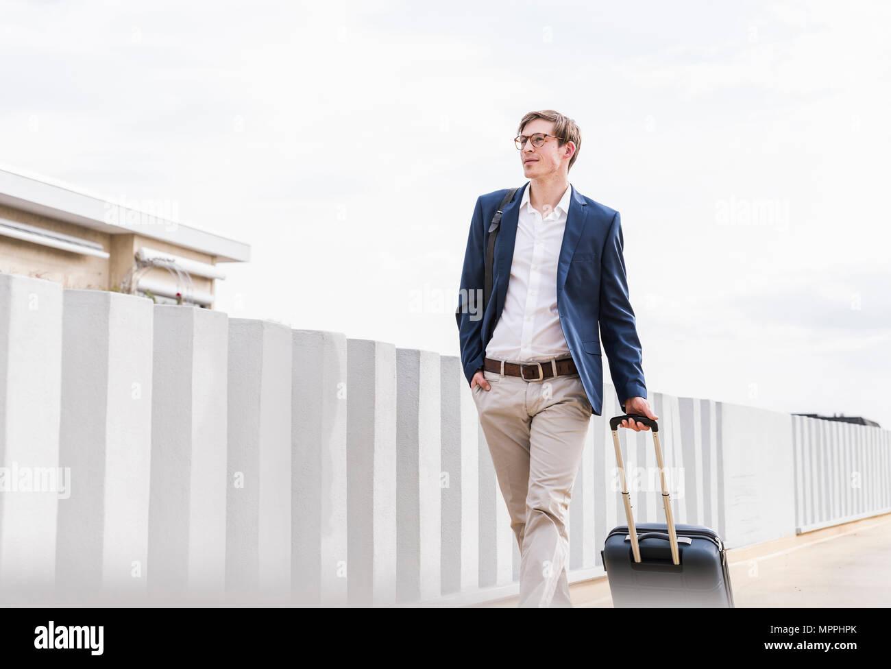 Confident businessman avec rolling suitcase marche à un garage de stationnement Photo Stock