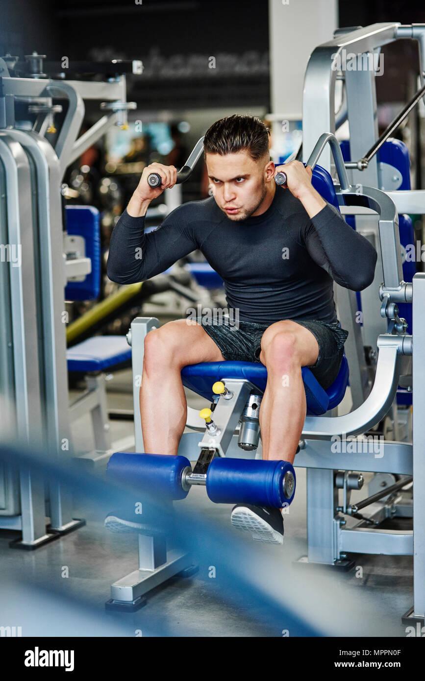La formation de l'homme avec machine d'exercice dans la salle de sport Photo Stock