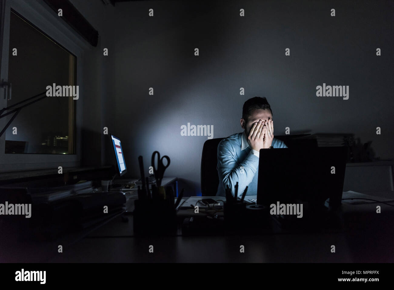 Épuisé businessman sitting at desk in office at night Photo Stock