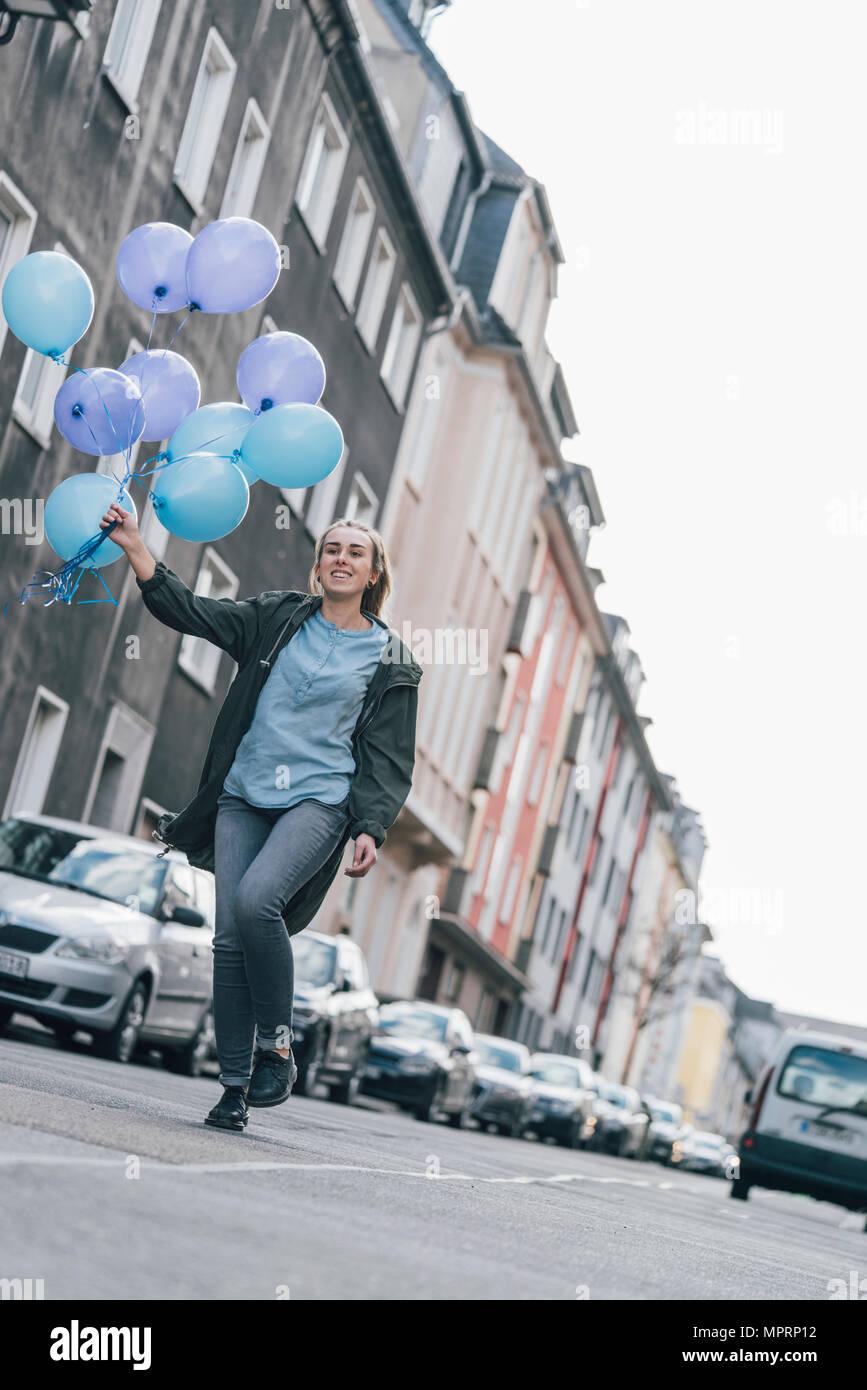 Femme heureuse avec des ballons bleu marche dans la rue Photo Stock