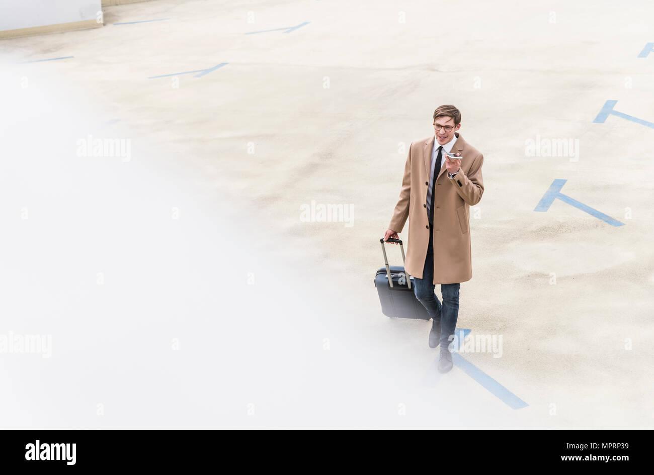 Businessman with rolling suitcase et smartphone marche à un garage de stationnement Photo Stock