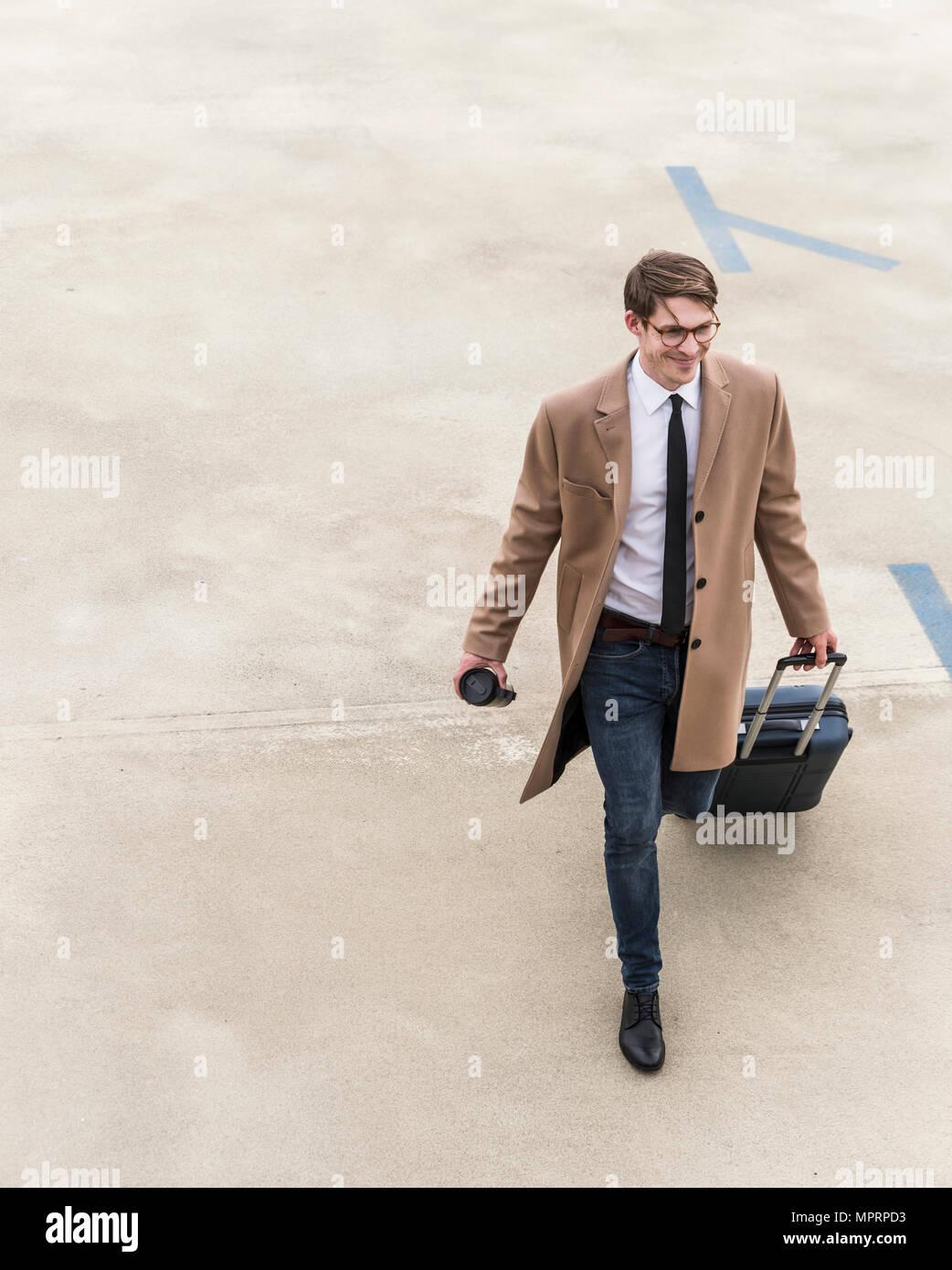 Smiling businessman with rolling suitcase marche à un garage de stationnement Photo Stock
