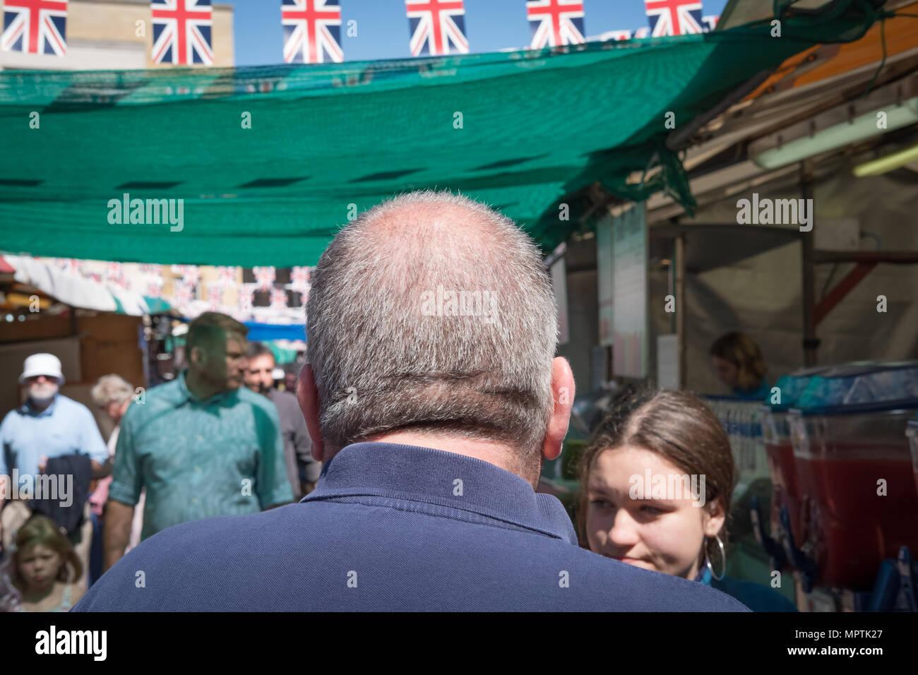 Close-up, l'accent peu profondes d'un homme adulte vu la marche loin de la caméra. Il est situé dans un marché en plein air au cours de la fête. Banque D'Images
