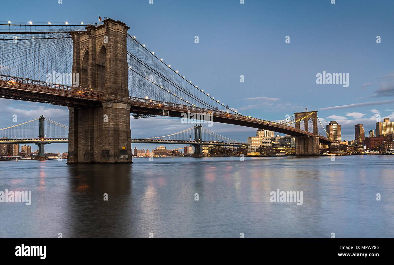 Le Pont de Brooklyn au coucher du soleil avec le Pont de Manhattan en arrière-plan span un calme East River. Photo Stock