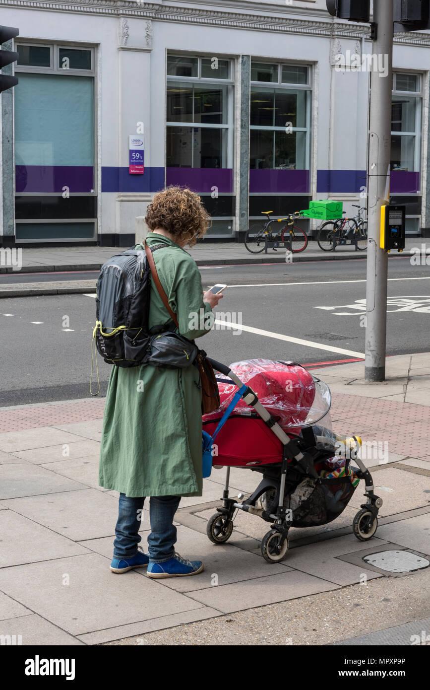 Une femme poussant une poussette avec un enfant tout en utilisant un téléphone mobile à côté de la rue portant un sac à dos et sms. maman et enfant. d'être mère. Photo Stock