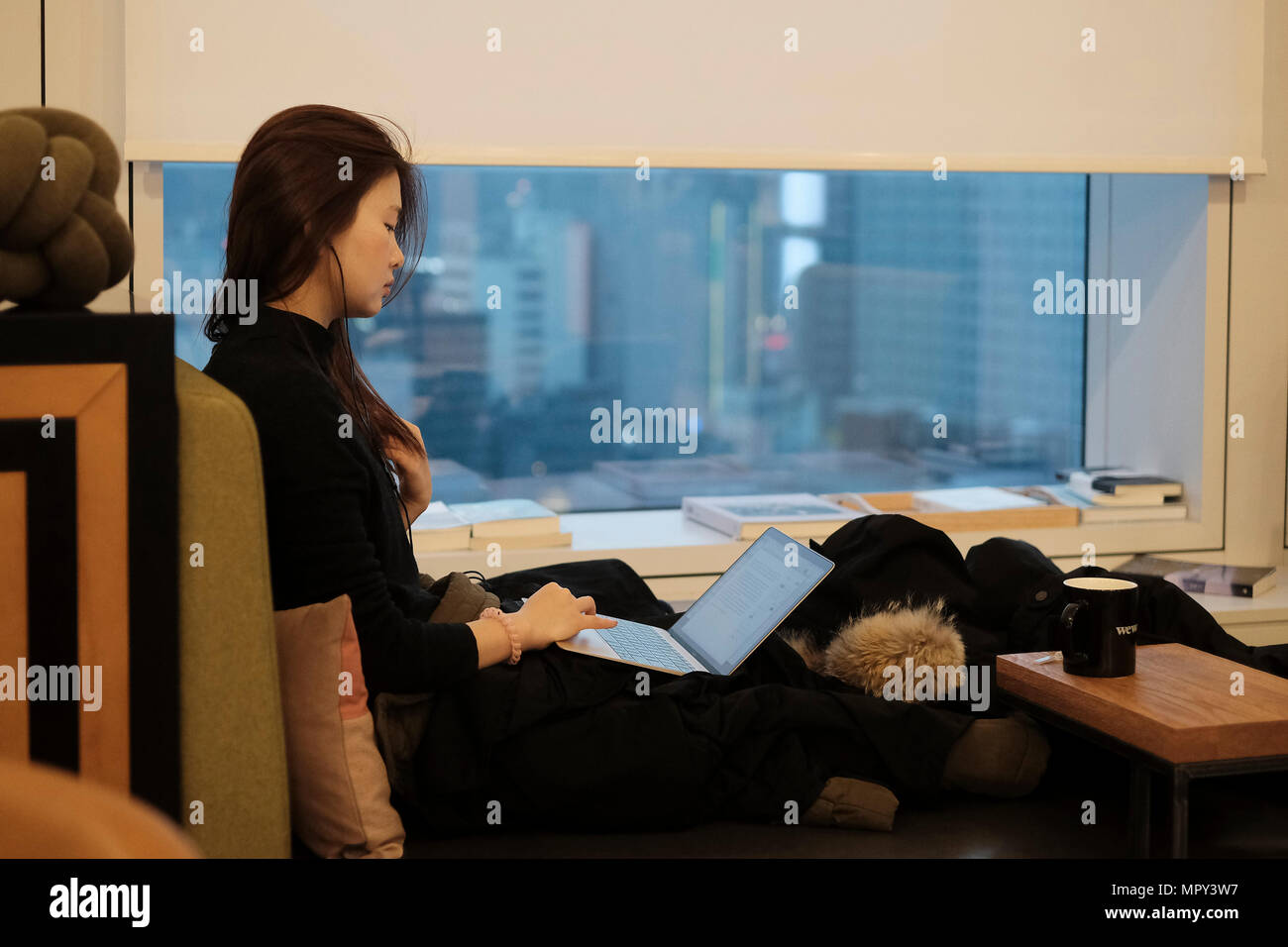 Une jeune femme coréenne à laide dun ordinateur portable dans l