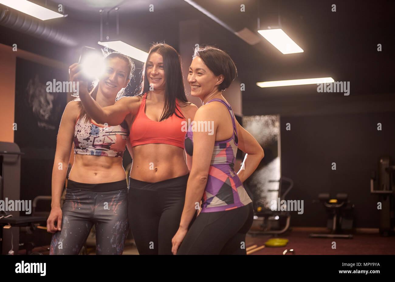 Certains amis féminins musculaire en tenant debout dans la salle de sport selfies Photo Stock