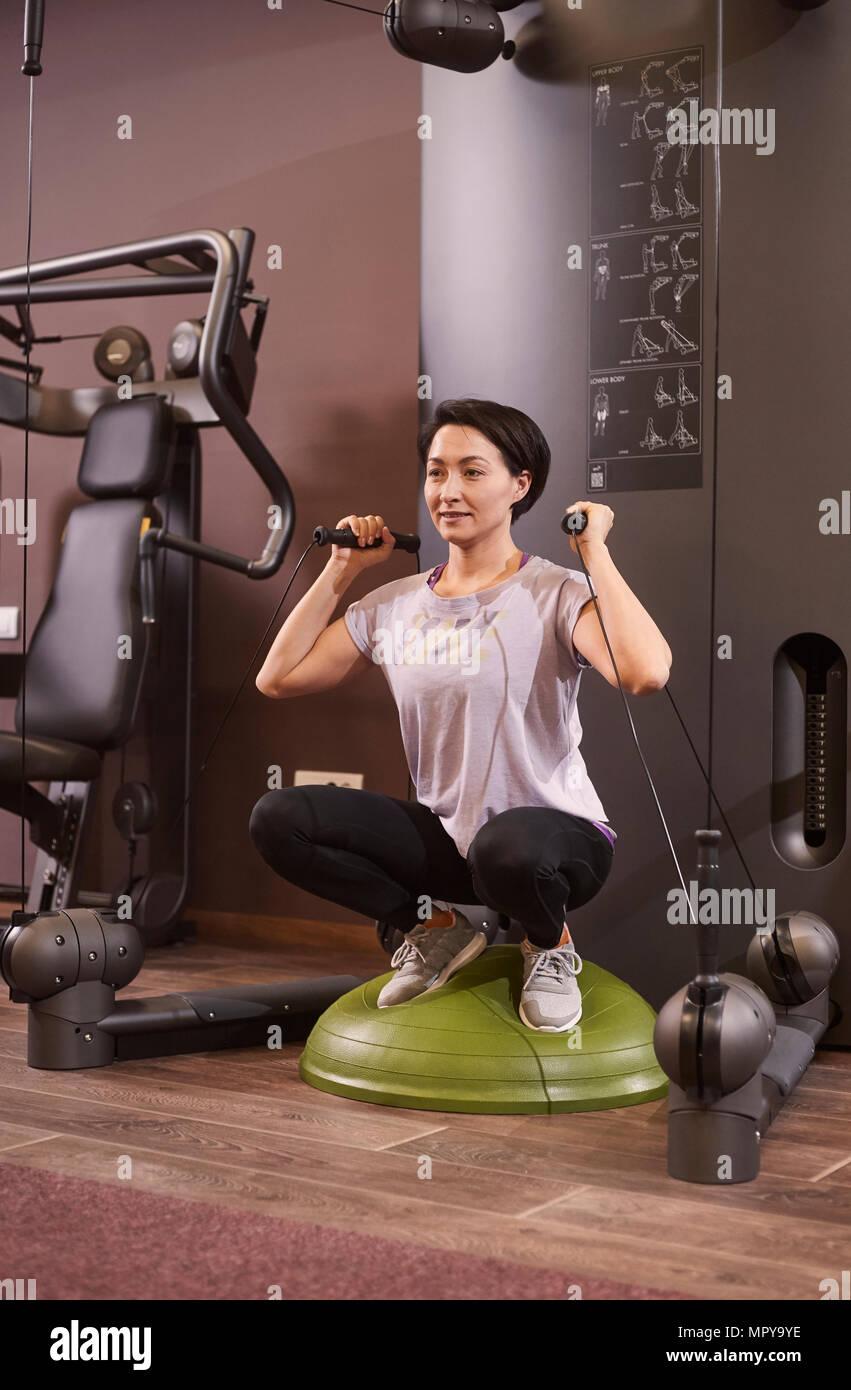 Femme l'entraînement avec bandes de résistance alors que l'équilibre accroupi sur ball at gym Photo Stock
