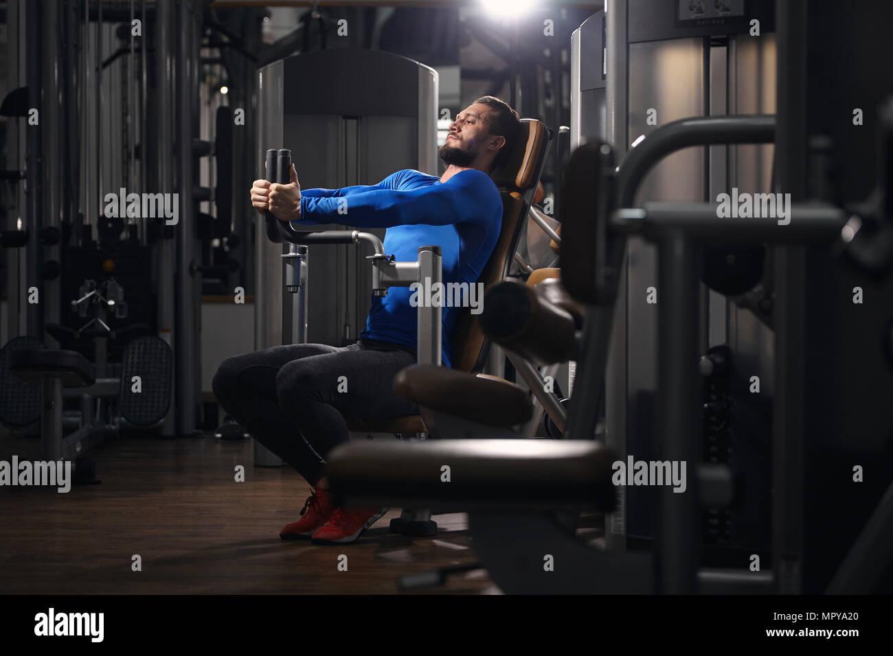 L'homme s'étend sur machine d'exercice à la salle de sport Photo Stock