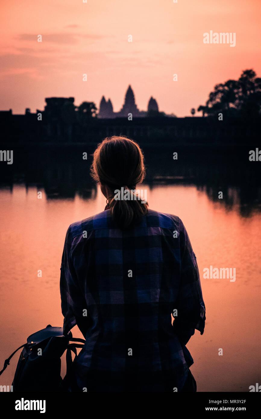 Les femmes adultes avec dos à la caméra observe le lever du soleil reflétée à travers le lac à Angkor Wat Temple complexe, Angkor, Siem Reap, Cambodge, Asie du sud-est Photo Stock