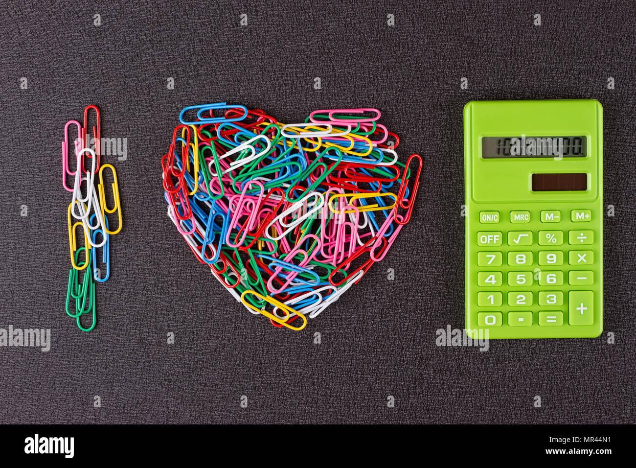 Les trombones sont alignés en forme de cœur et d'une calculatrice Photo Stock