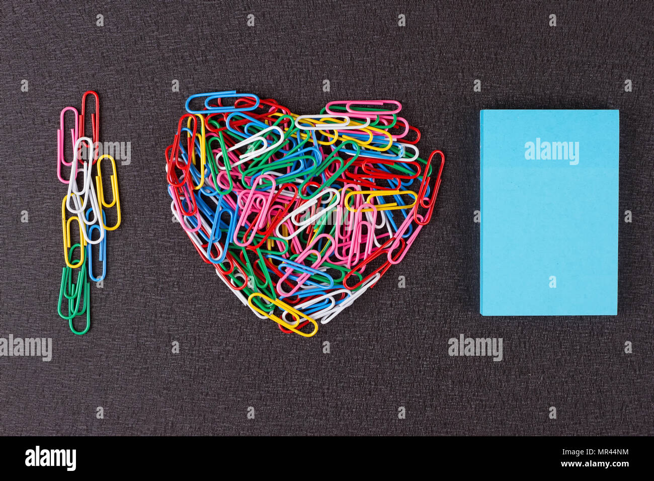Variété de trombones de couleurs disposées en forme de coeur sur fond noir. Photo Stock