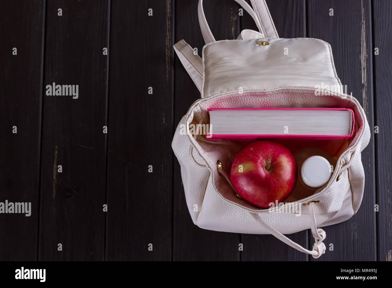 e24c9d294a Sac à dos en cuir blanc, livre rose, une bouteille d'eau sur un fond noir