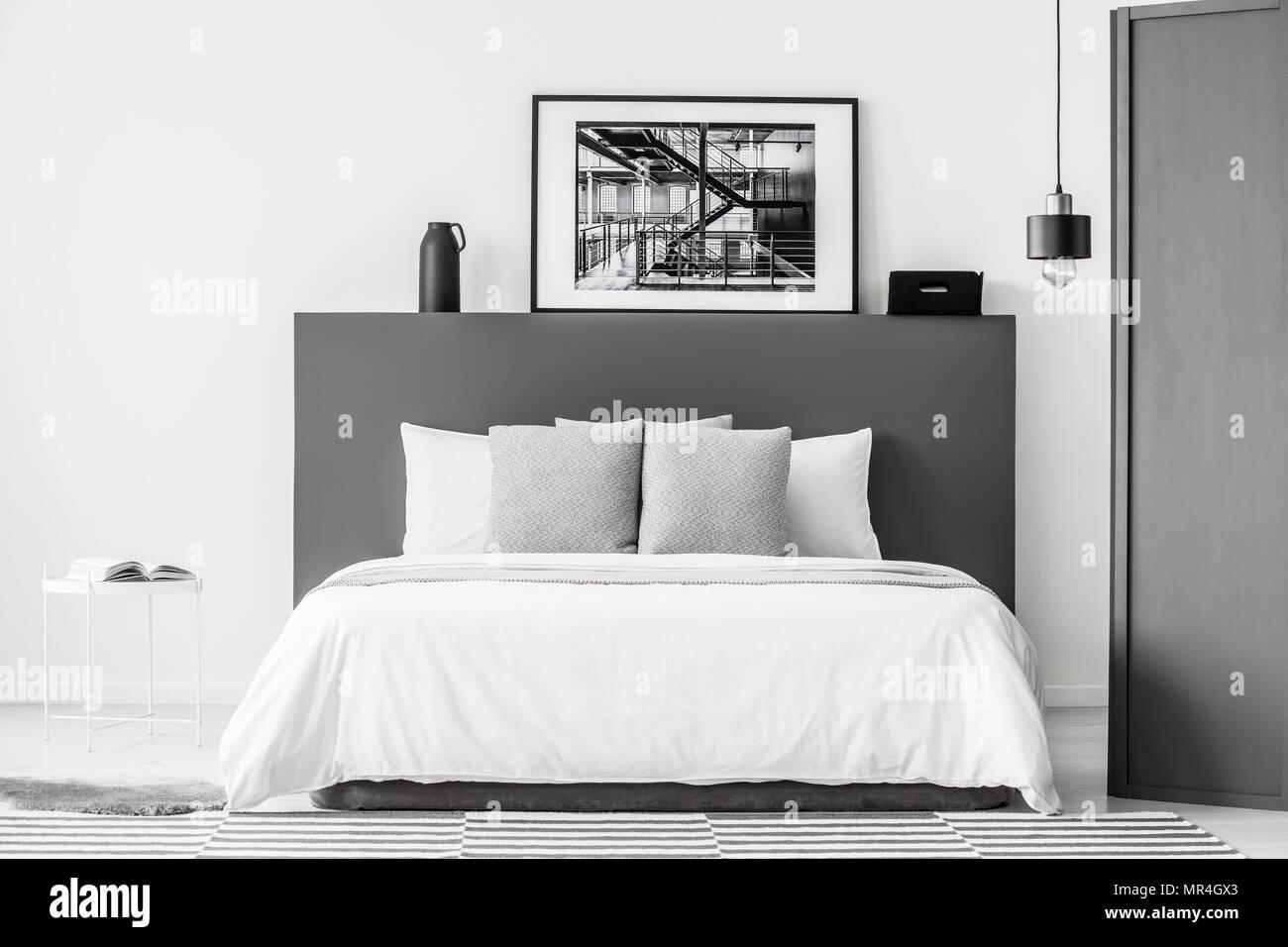 Coussins à motifs sur lit dans chambre gris et blanc avec l ...