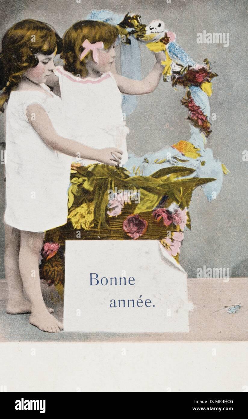 Nouvelle année française carte postale représentant deux jeunes filles, avec un panier de fleurs 1900 Photo Stock