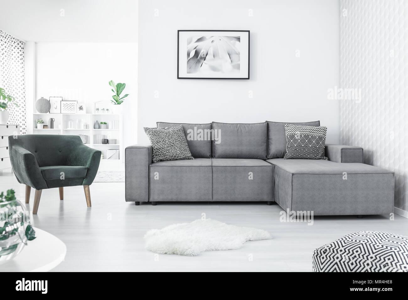 Fauteuil gris et canapé d\'angle, la peinture sur le mur blanc et ...
