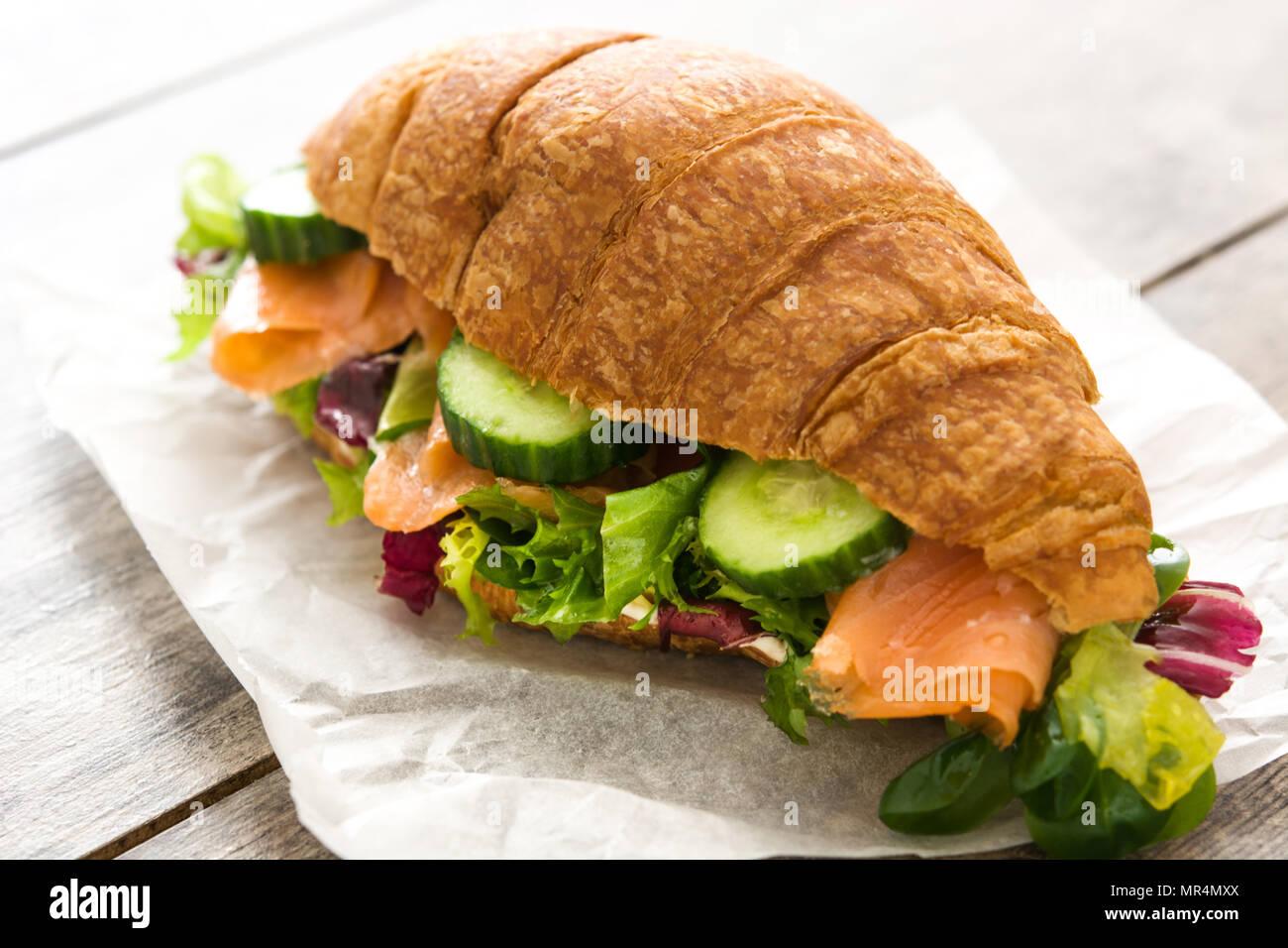 Sandwich croissant avec le saumon et les légumes sur la table en bois. Photo Stock