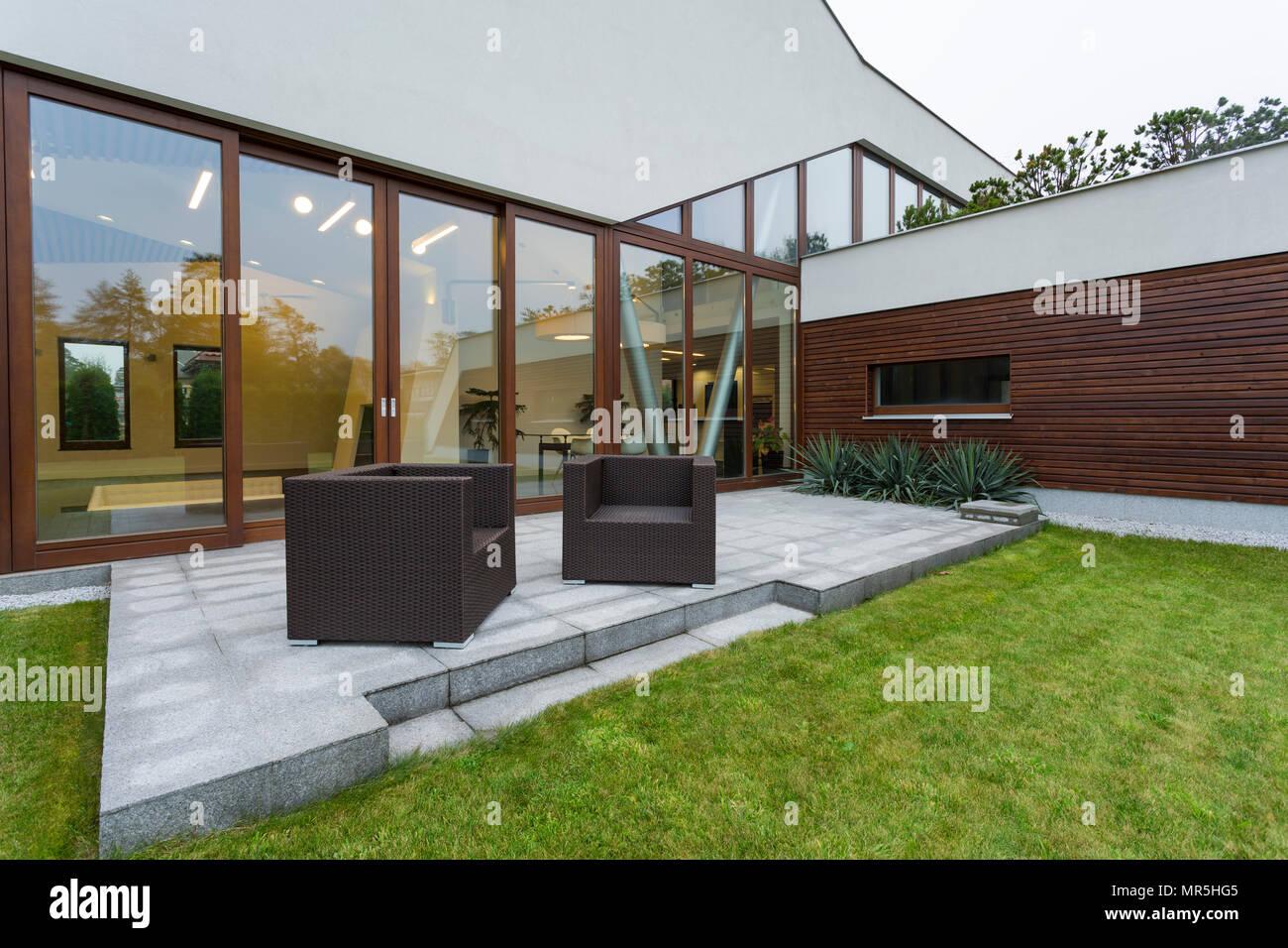 Maison Moderne Avec Patio Extérieur, Mobilier En Rotin Et Mur Fenêtre