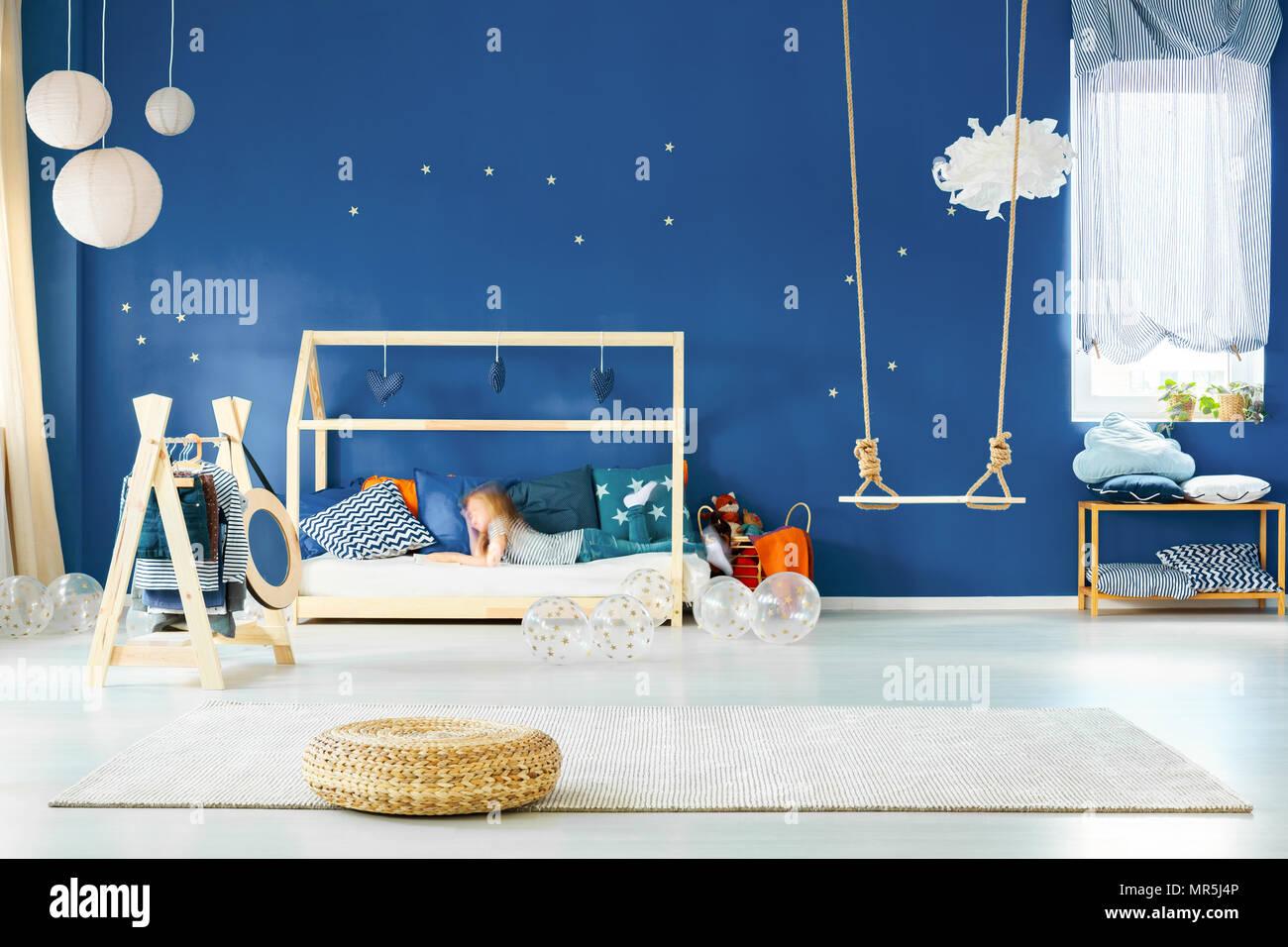 Jeune fille moderne avec swing, lit et mur bleu marine Banque D'Images