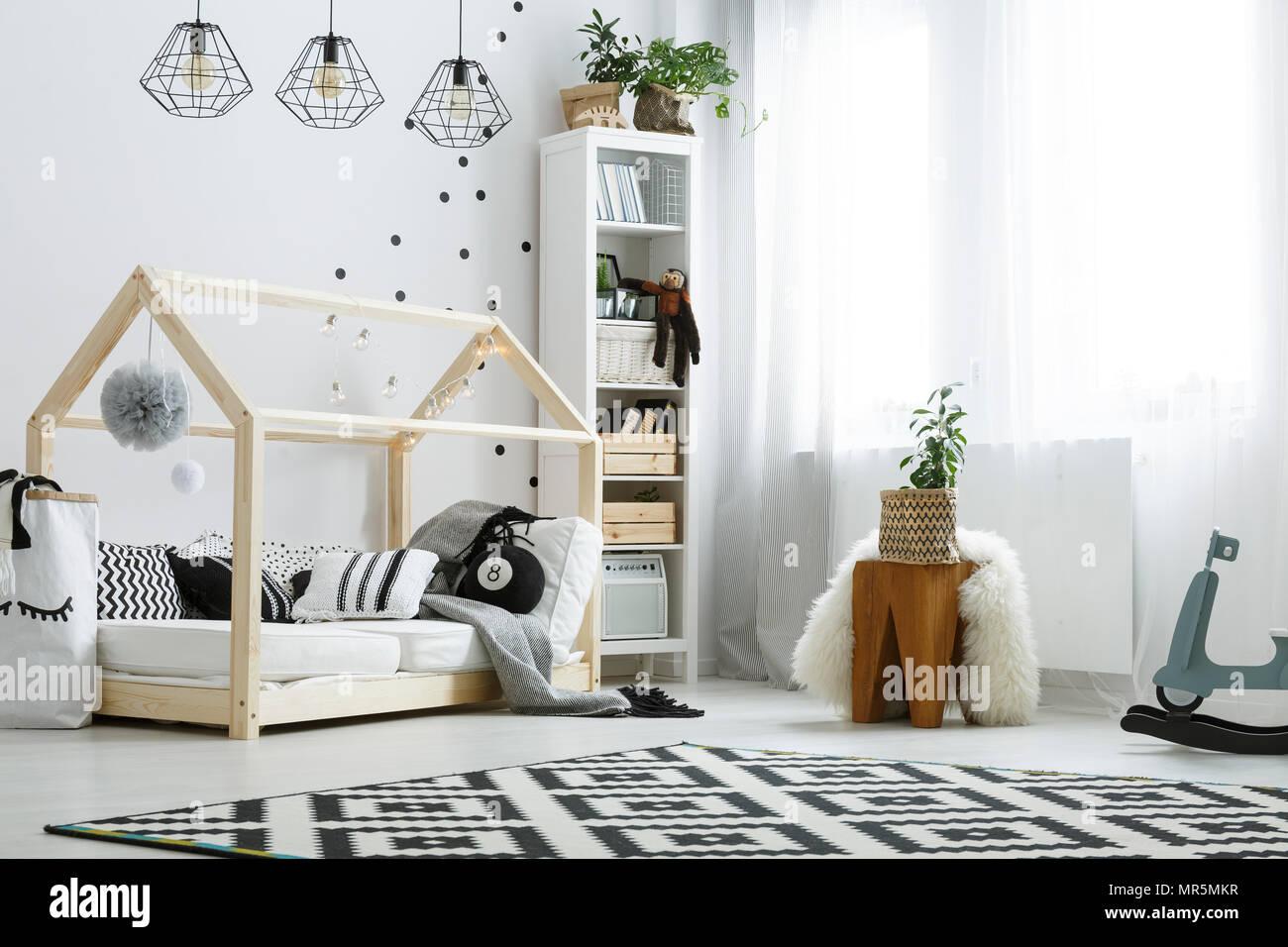 Chambre blanche avec un lit en bois, lampes, tapis et bibliothèque ...