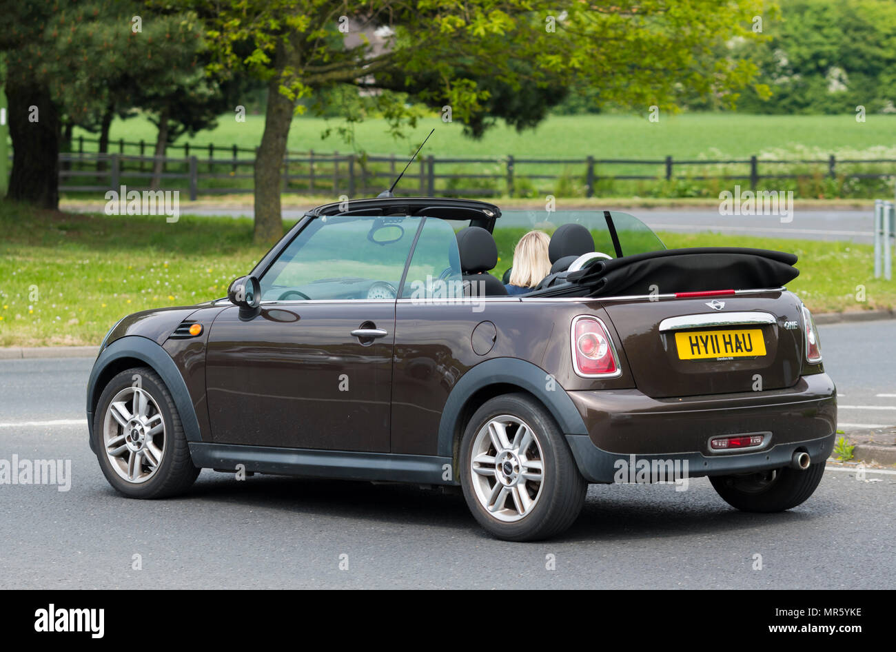 Open top cabriolet mini voiture avec le haut vers le bas conduit par une femme en été au Royaume-Uni. Photo Stock