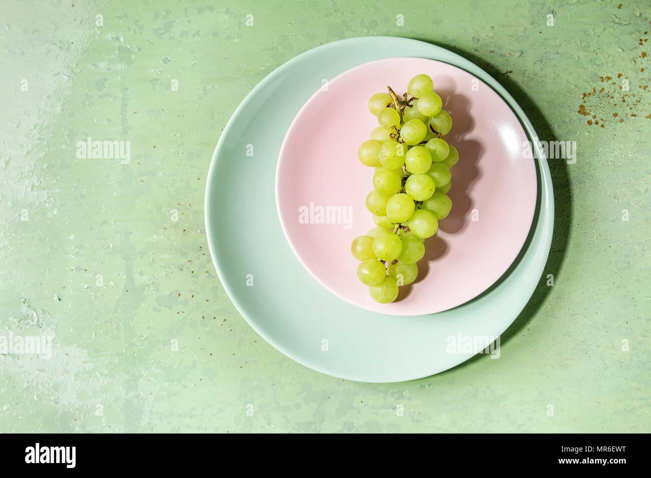 Tas de raisins verts mûrs sur plaque sur turquoise pastel vert pin-up arrière-plan. Copier l'espace. Vue d'en haut Photo Stock