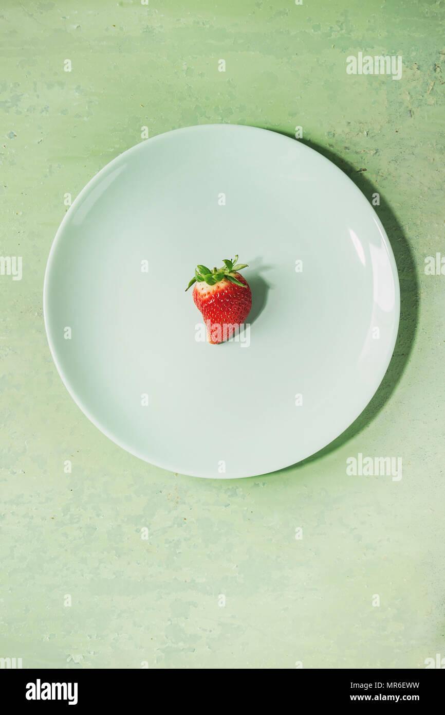 Des fraises fraîches sur plaque sur turquoise pastel rose pin-up arrière-plan. Copier l'espace. Vue d'en haut Photo Stock