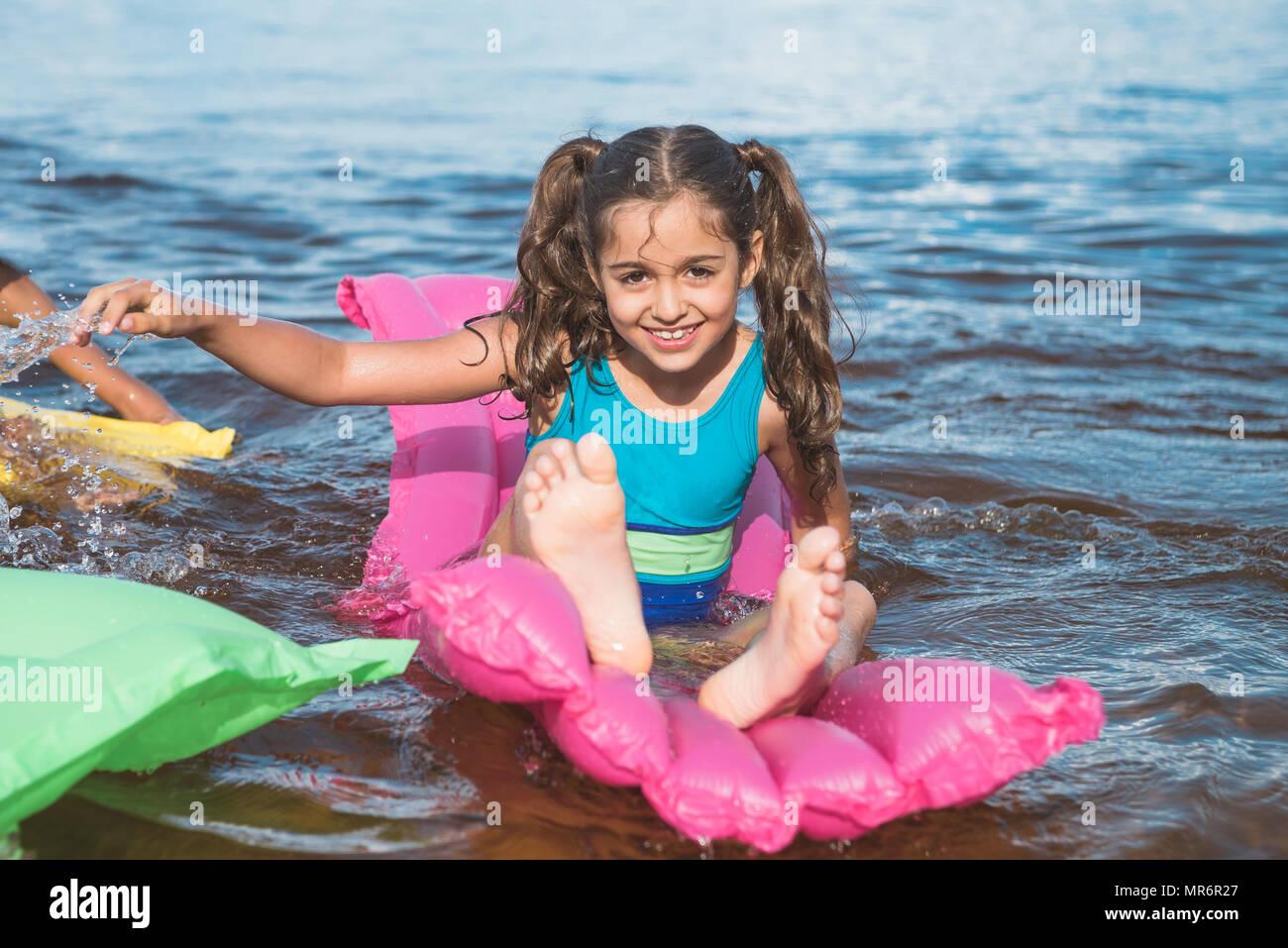 Petite fille joyeuse natation sur matelas gonflables en mer Photo Stock