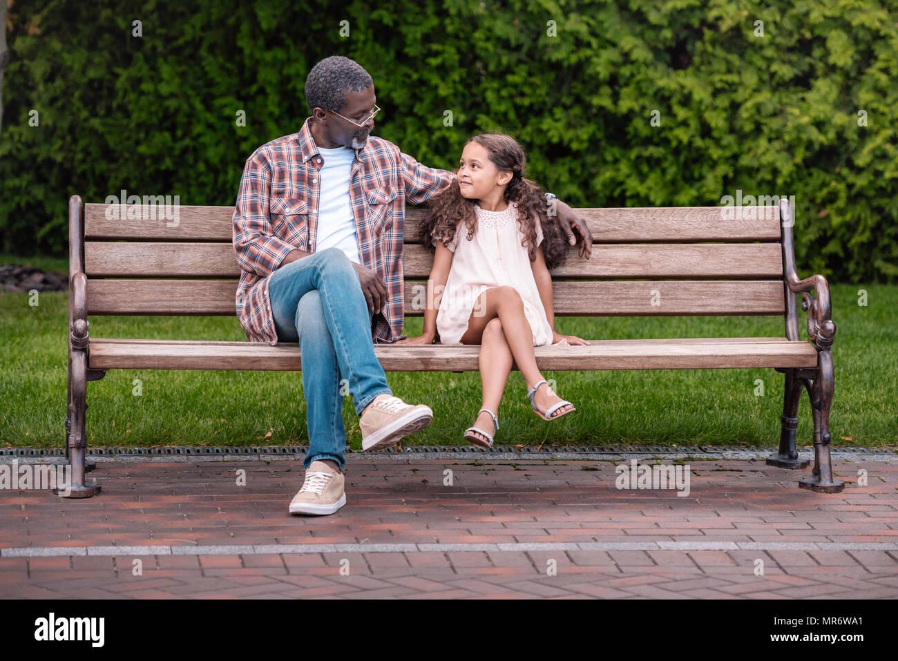 Adorable african american girl et son grand-père assis sur un banc dans le parc Photo Stock