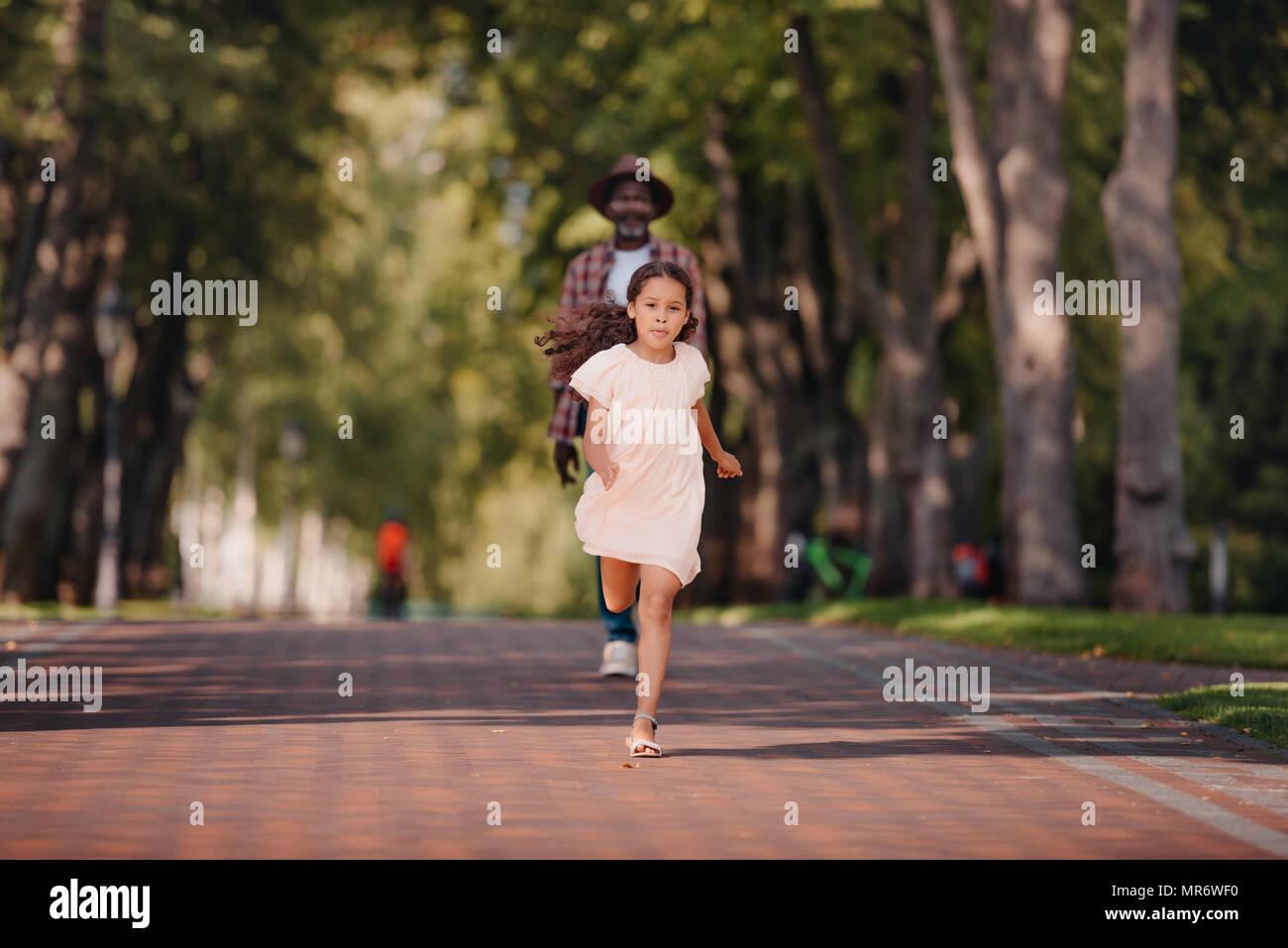 Cute african american girl en marche et passer du temps avec son grand-père dans la région de park Photo Stock
