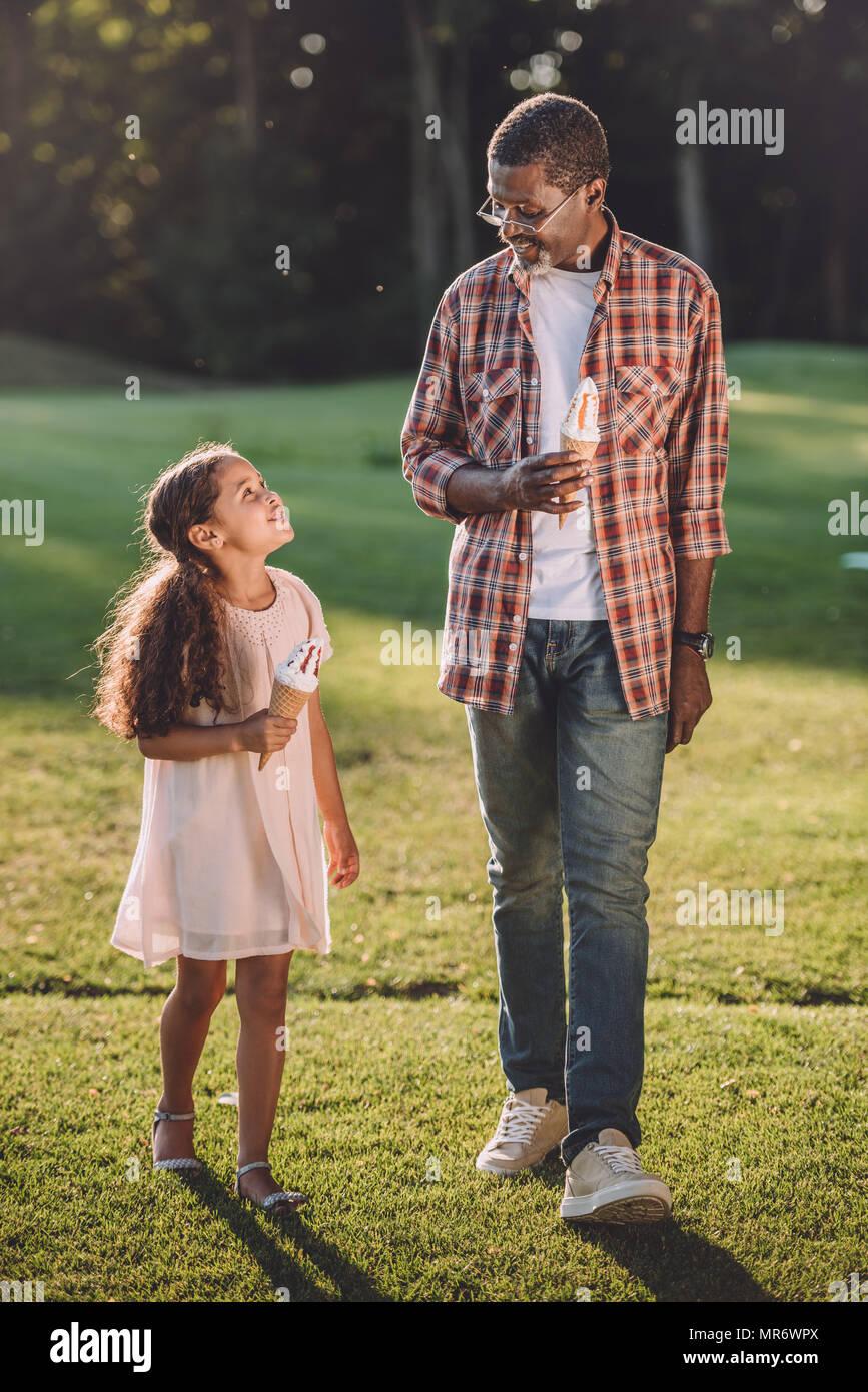 Smiling african american petite-fille et grand-père de manger de la crème glacée dans des cônes en marchant dans le parc Photo Stock
