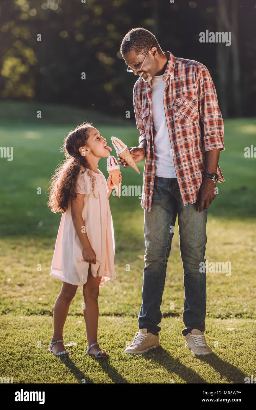 Happy african american girl et grand-père de manger de la crème glacée dans des cônes en marchant dans le parc Photo Stock