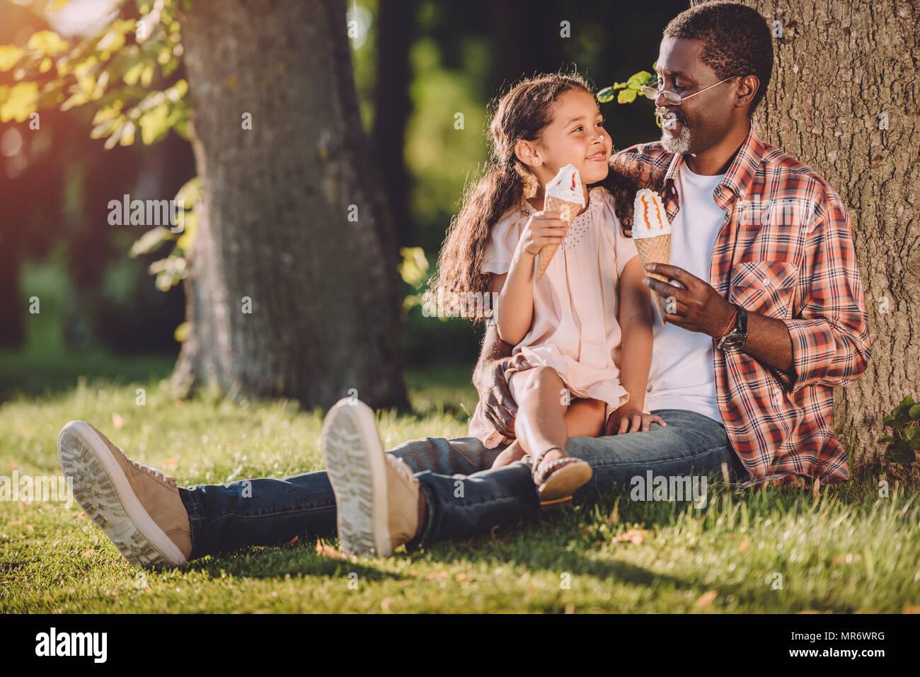 Happy african american petite-fille et grand-père de manger de la crème glacée dans des cônes alors que sitting on grass in park Photo Stock