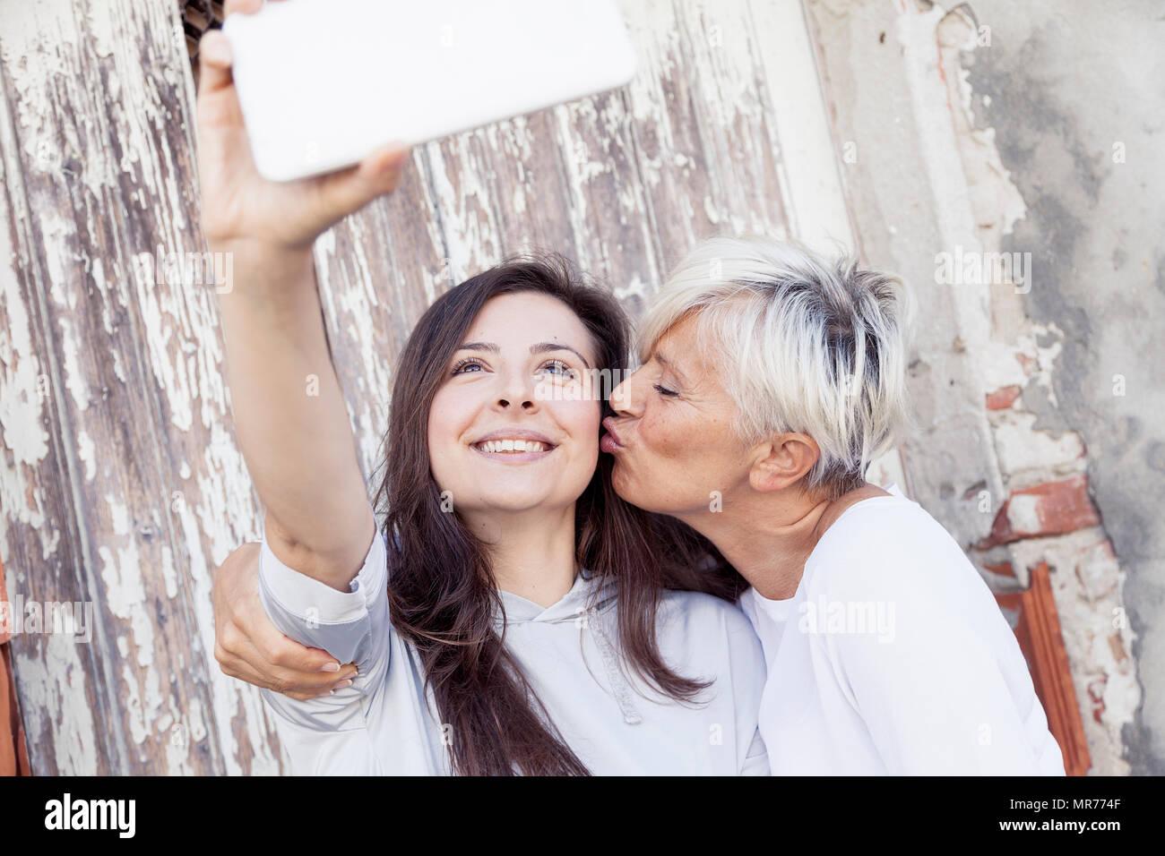 Mère et fille adultes prendre un extérieur selfies Photo Stock