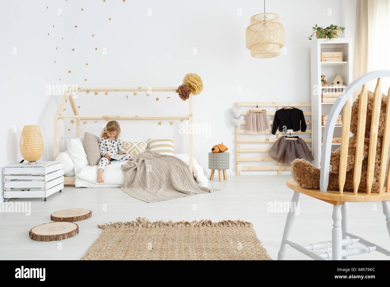 Petite fille assise sur son lit dans la chambre à coucher scandinave ...