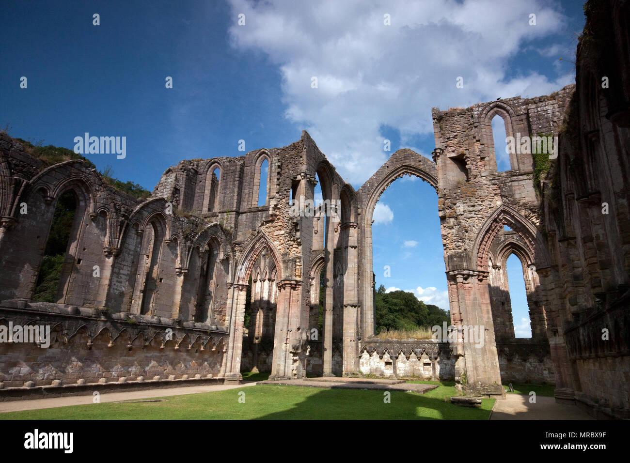 Avec l'architecture gothique grand archs dans l'intérieur du monastère en ruines de l'abbaye de Fountains, Ripon, UK Photo Stock
