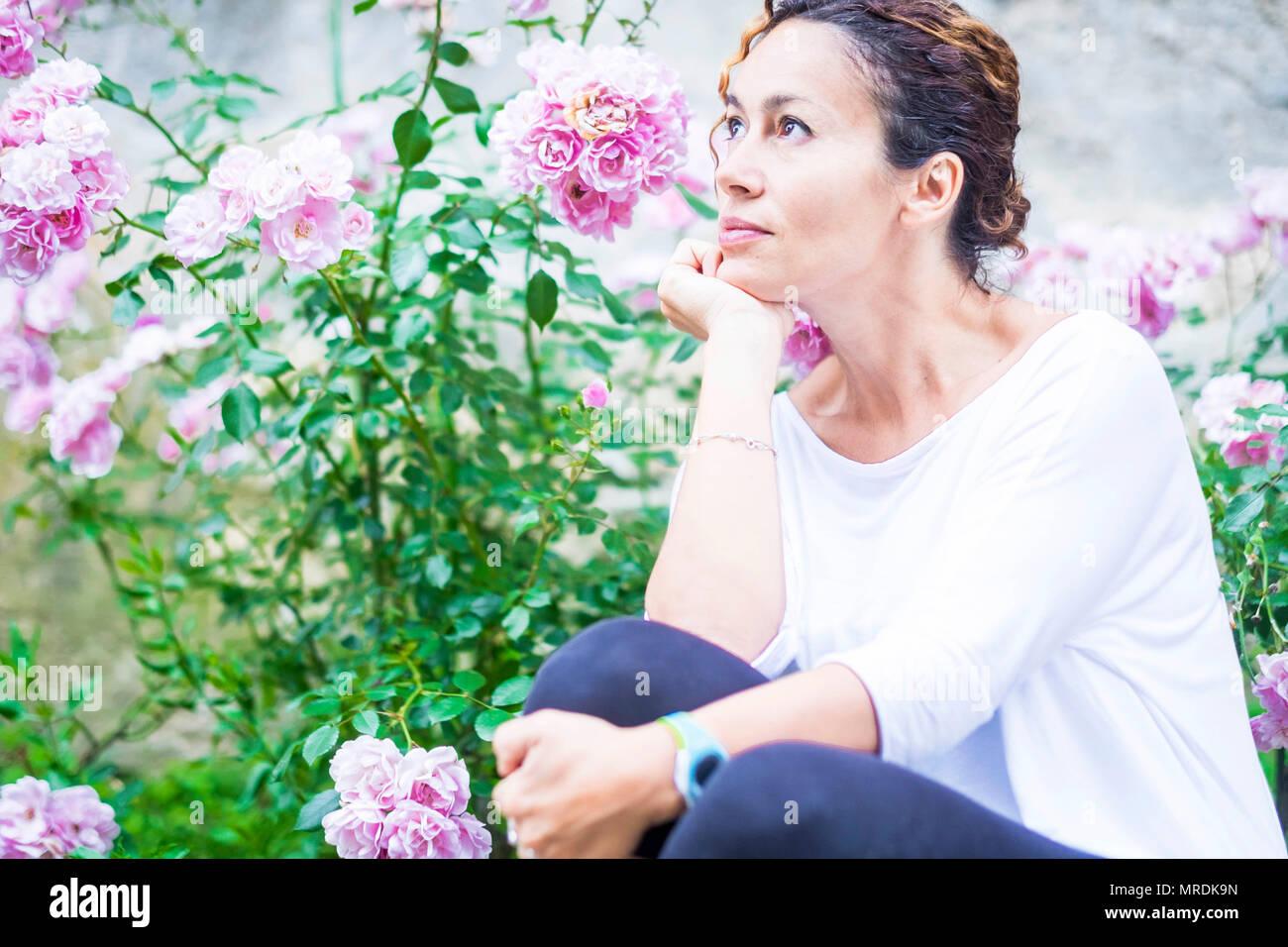 Belle wooman 40 ans regarde sa pensée latérale heureux. Fond de fleurs roses. Couleurs Nature plein air. Banque D'Images