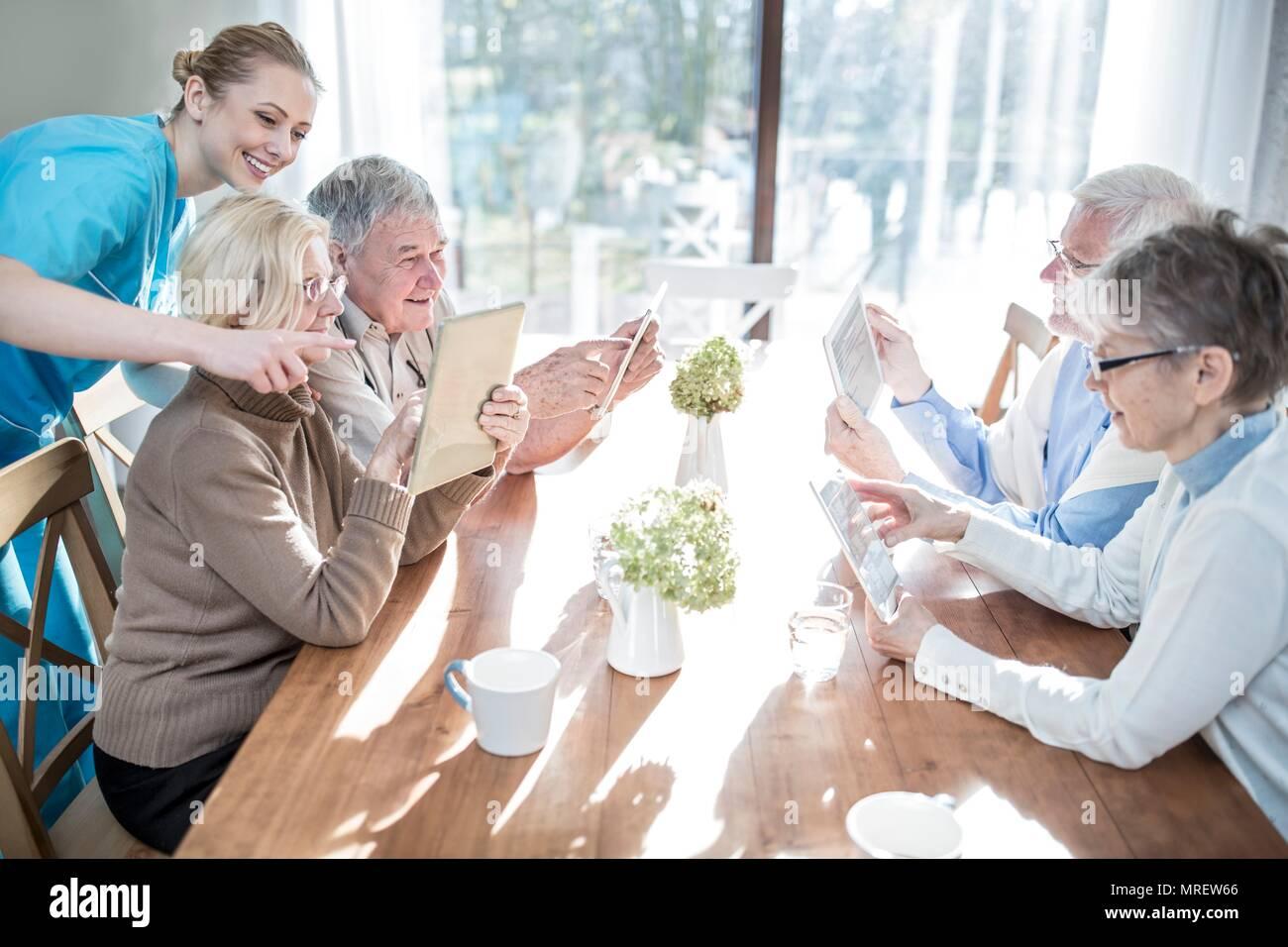 Des aînés à l'aide de tablettes numériques en maison de soins. Photo Stock