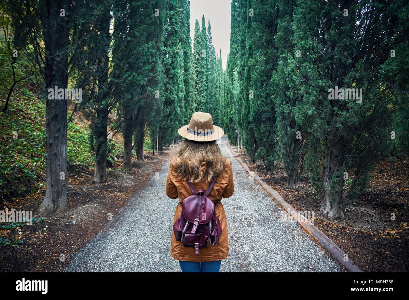 Femme au chapeau brun avec sac à dos à la recherche à l'allée de cyprès dans le jardin botanique de Tbilissi, Géorgie Photo Stock