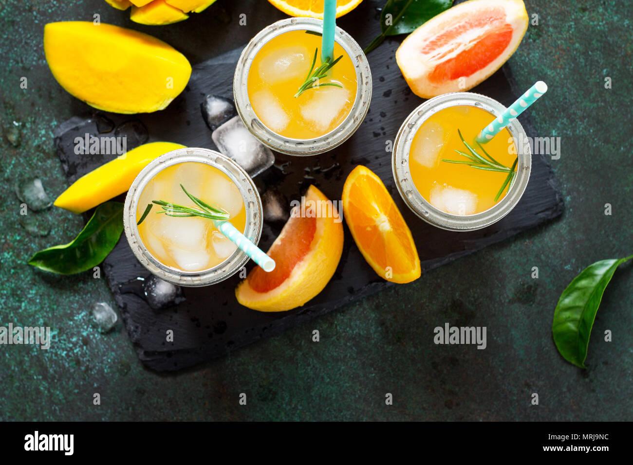 Des cocktails d'été d'agrumes et de mangue, boisson froide ou un verre avec de la glace sur une pierre sombre arrière-plan. Banque D'Images