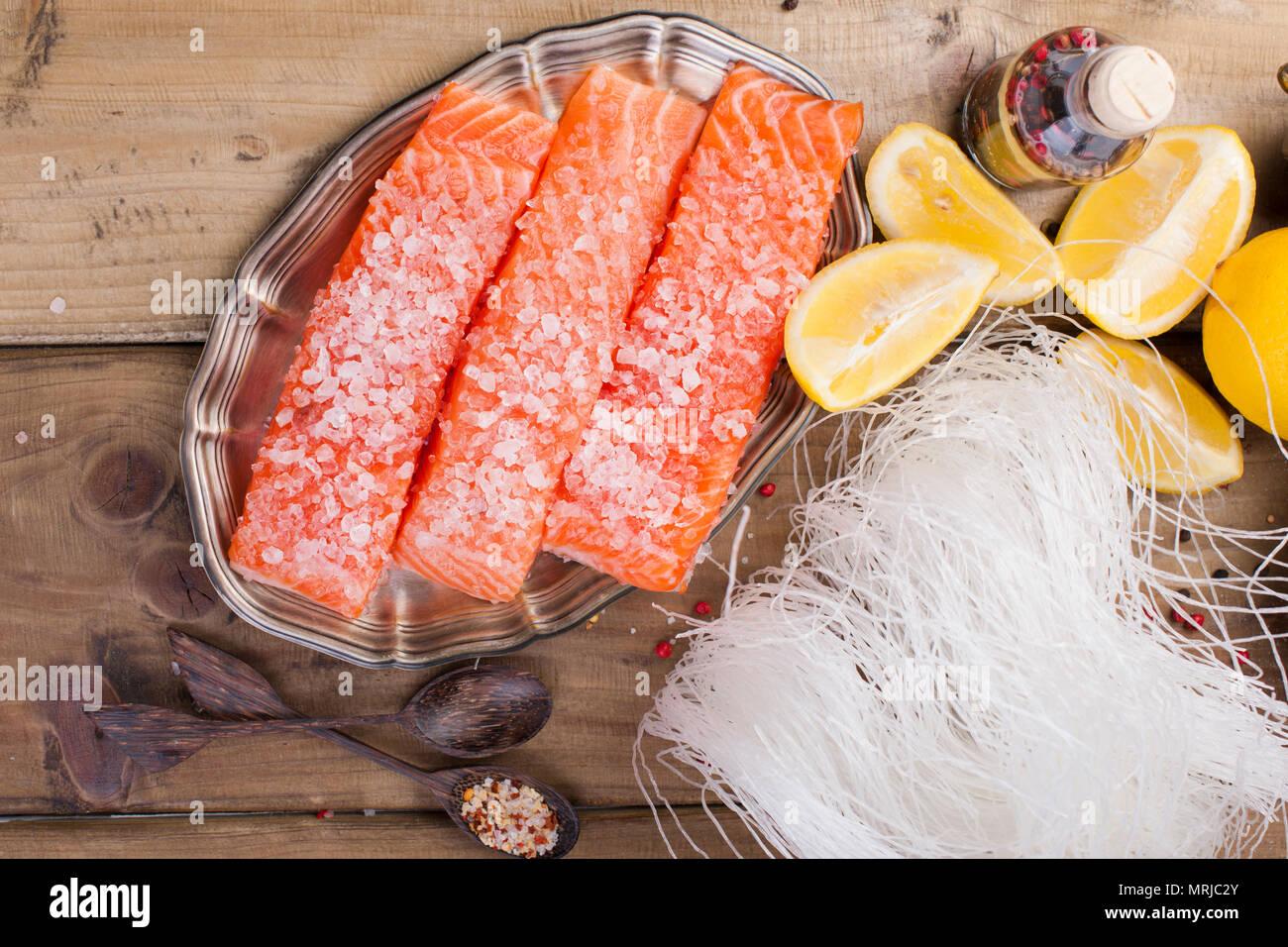 Filet de saumon cru avec du poivre de ris de veau et de sel sur du papier sulfurisé thème rustique avec copie-espace. Mise à plat. Photo Stock