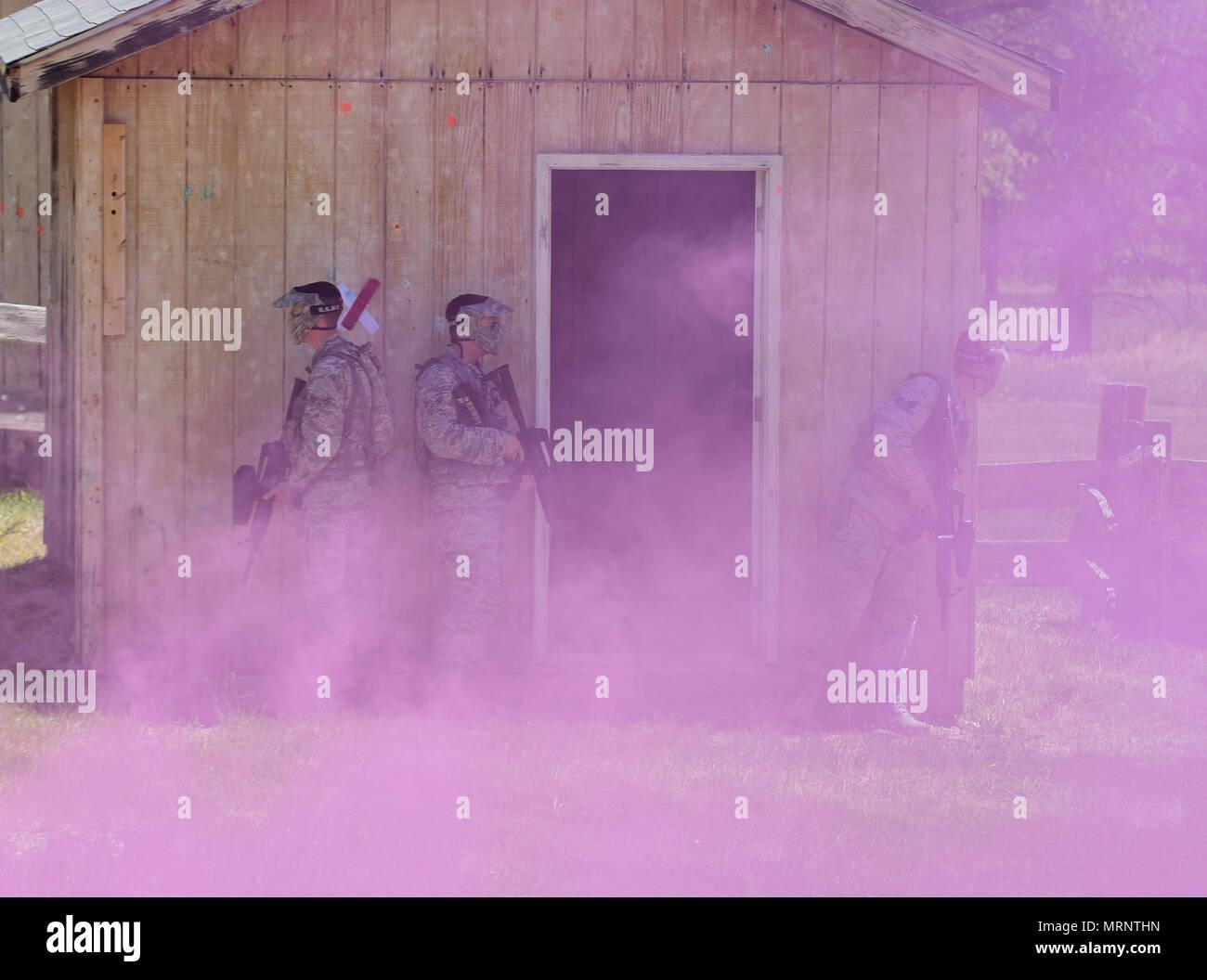 Une escouade de 28e Escadron de génie civil d'aviateurs se tenir derrière un bâtiment violée attendent pour dissiper la fumée à une simulation de village à une formation de la Garde nationale du Dakota du Sud le 19 juin, 2017 du site. Les Aviateurs utilisé l'aboutissement de leur formation pour exécuter des ordres pour effacer la simulation d'un village d'adversaires et trouver une cache d'armes. (U.S. Photo de l'Armée de l'air par la Haute Airman James L. Miller) Photo Stock