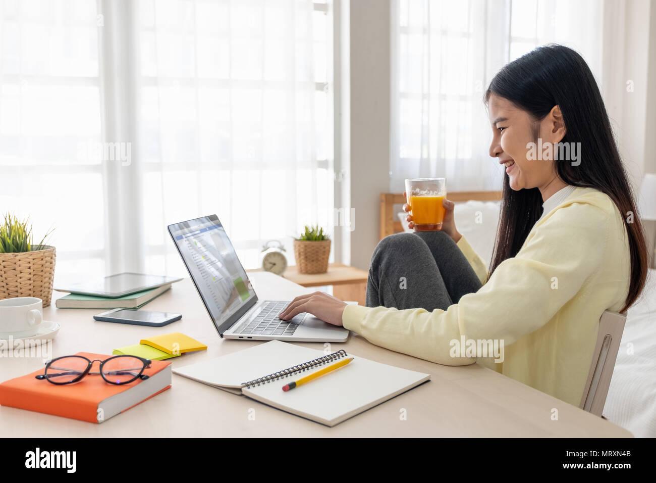 Femme d'origine asiatique s'asseoir genoux jusqu'utiliser les médias sociaux avec un ordinateur portable sur la table et de prendre un verre de jus d'orange dans la chambre à la maison.Travail à domicile travail à domicile.concept.rel Photo Stock