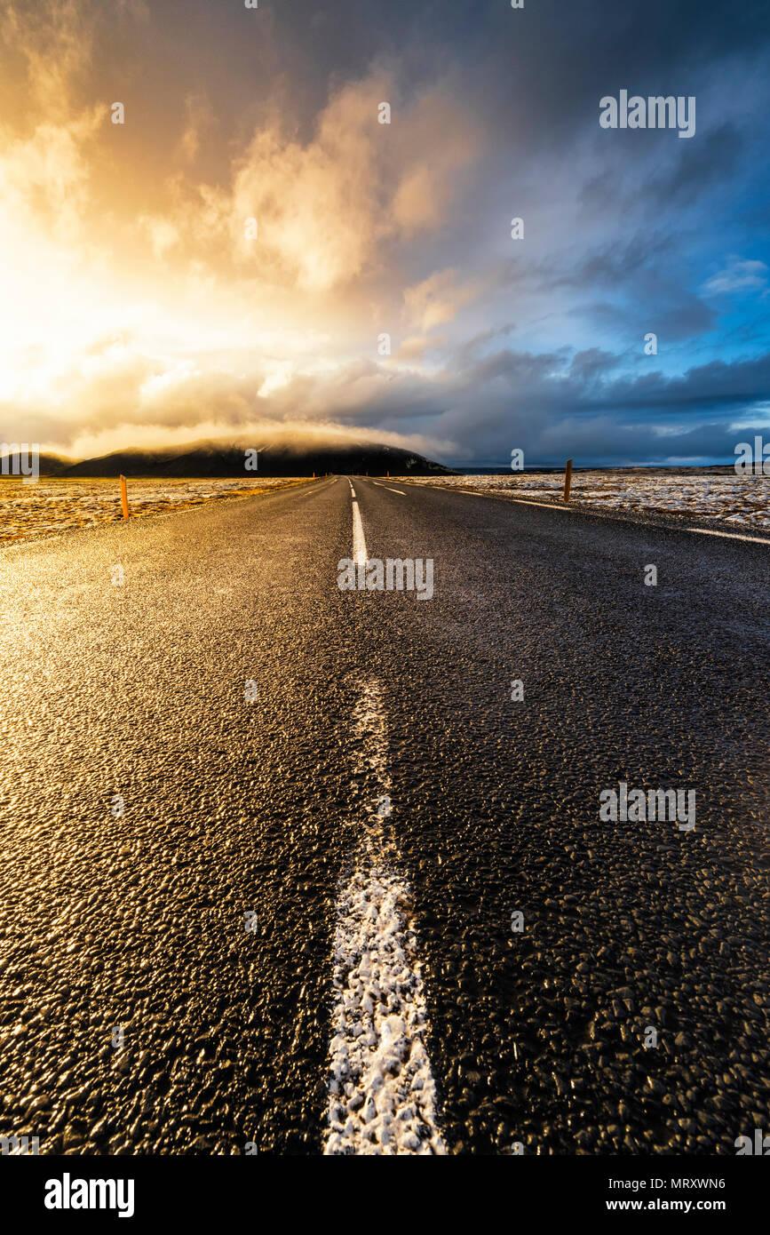 L'Islande, le nord de l'Europe. Une route pavée avec ciel dramatique Photo Stock
