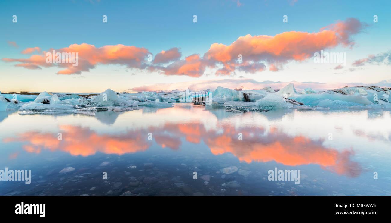 L'Est, l'Islande, l'Islande, le nord de l'Europe. L'emblématique peu icebergs dans la lagune bordée de glaciers au cours d'un lever du soleil Photo Stock