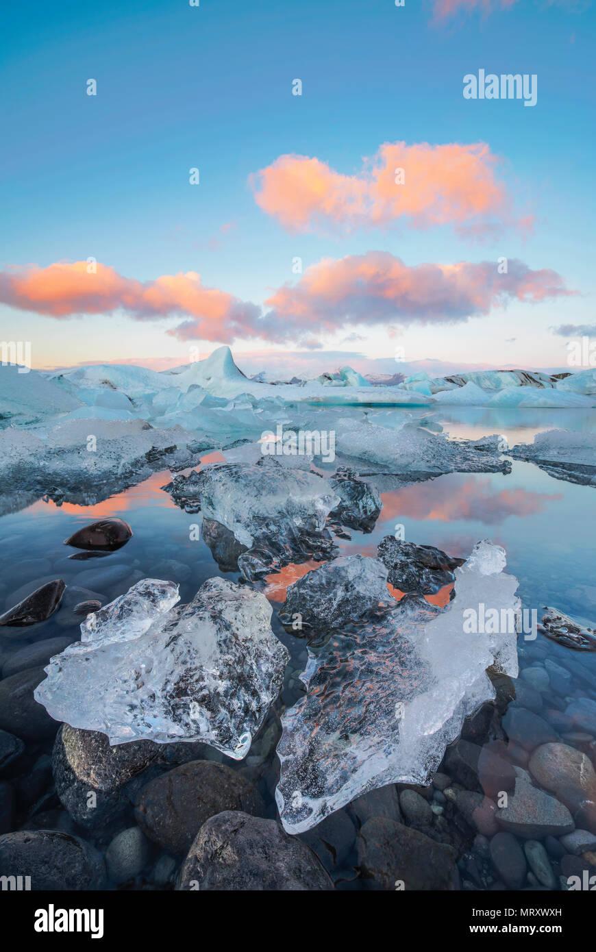 L'Est, l'Islande, l'Islande, le nord de l'Europe. L'emblématique peu icebergs dans la lagune bordée de glaciers au cours d'un lever du soleil Banque D'Images