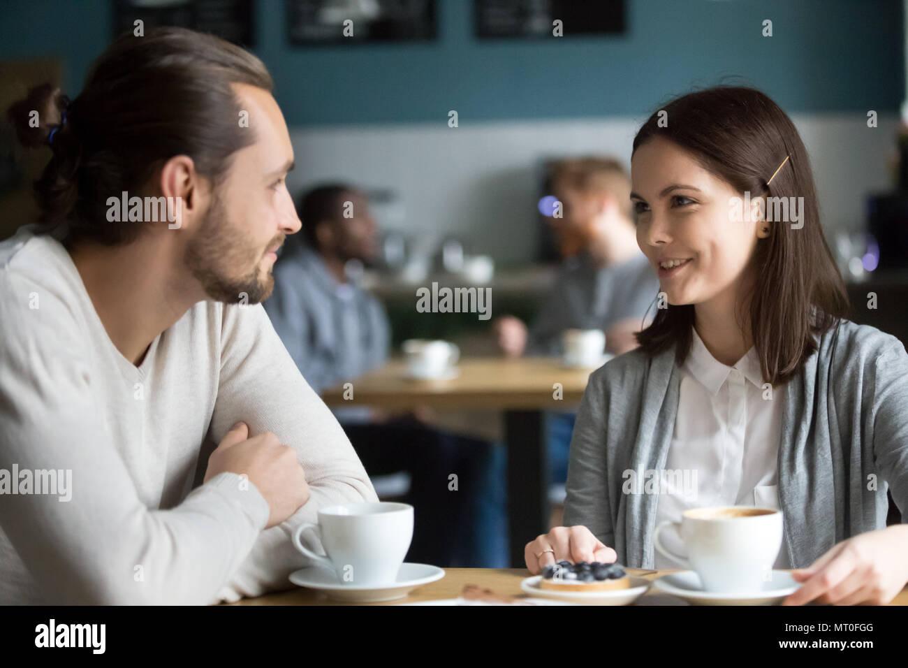 Heureux couple millénaire dans aime parler flirting at cafe table Photo Stock